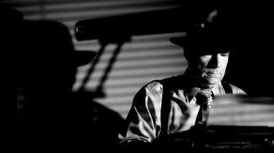 stock-footage-a-man-in-a-fedora-typing-on-a-vintage-manual-typewriter-film-noir-style-lighting